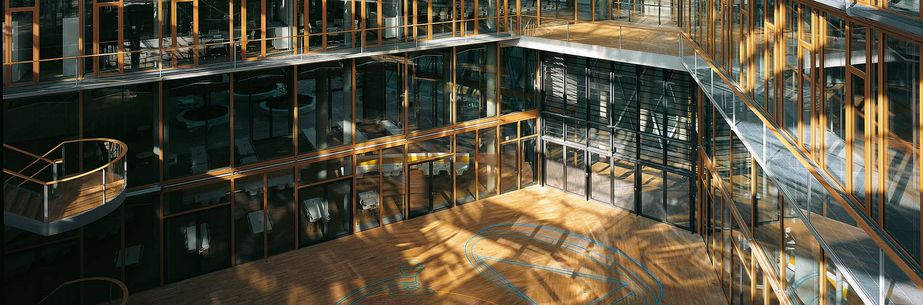 Entrance hall of a large company building, wooden floor and window frames, wooden staircase, light-flooded room