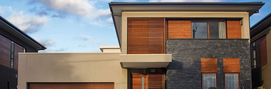 modern family house in gray and brown with wooden paneling and wooden windows