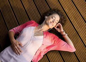 a woman lies on a wooden floor and listens to music